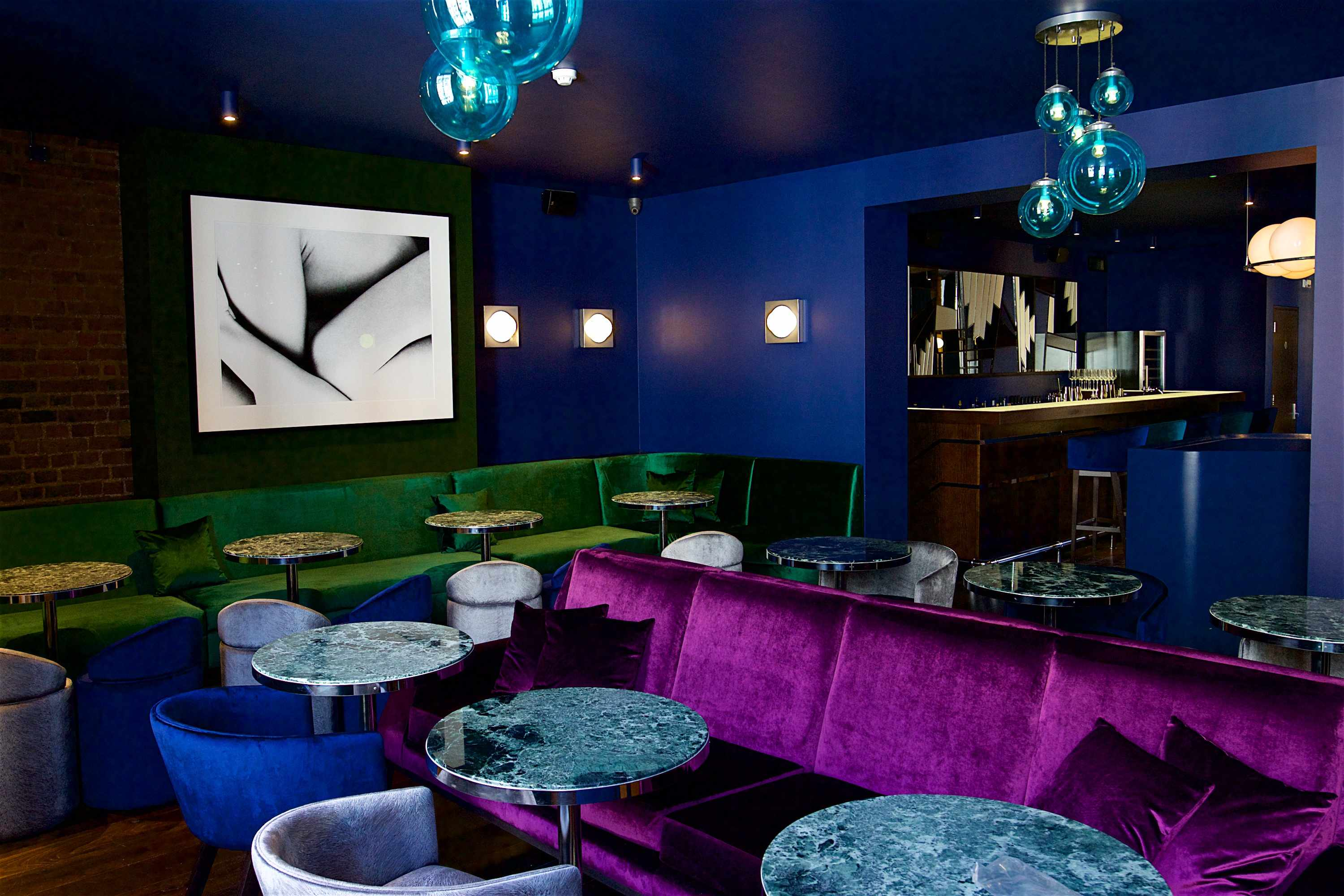 A room with darkly blue walls, purple seating and marble tables