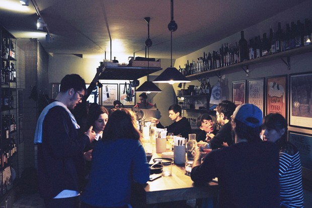 A dark room has one long central table. People are sat around the table drinking wine and eating food