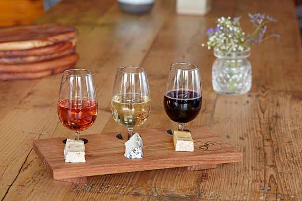 A wooden table is topped with a thin wooden tray. On top of the tray are three tasting glasses of wine with a chunk of cheese next to each one