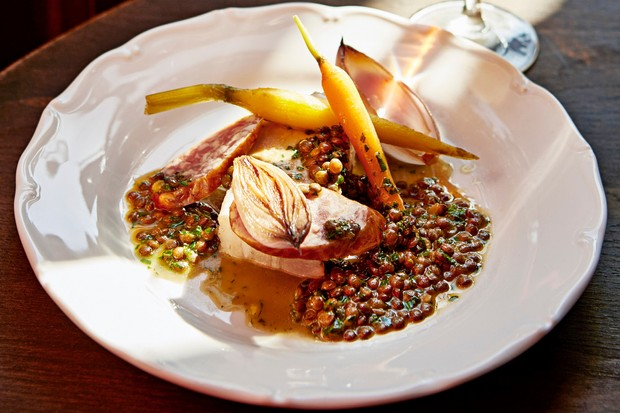 A white circular plate is topped with lentils and roasted carrots. There is a glass of wine in the background