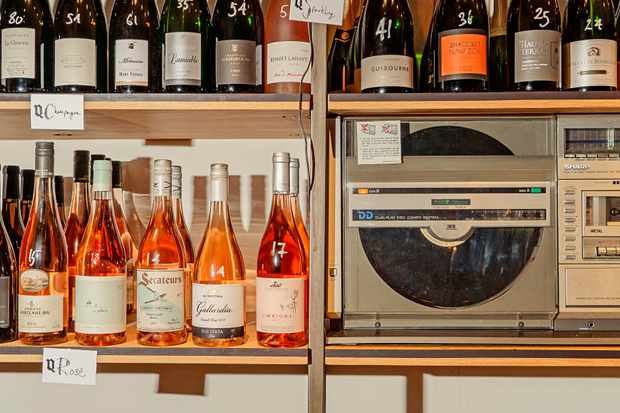 A wooden shelving unit has bottles of wine filling it. Next to it is a vintage record player