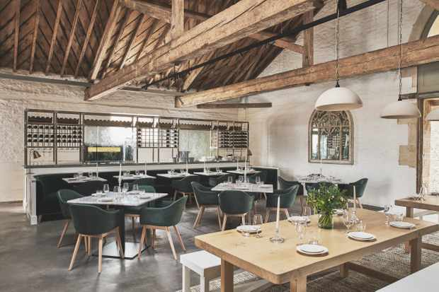 Interiors at the Ox Barn at Thyme. Striking exposed beams, marble tables with sea green armchairs and a large wooden bench table at the forefront