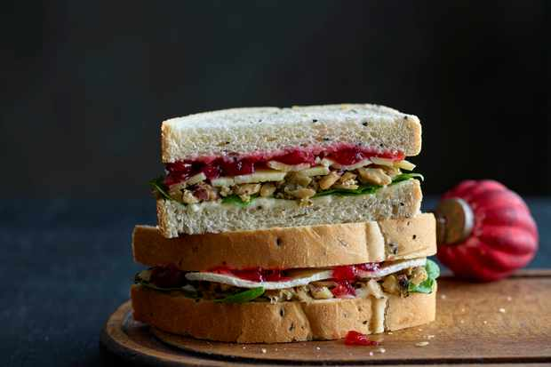 Two sandwiches stacked on top of each other with brie and cranberry sauce