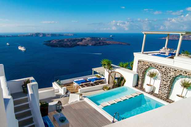 A hotel pool looking out over blue sea in Santorini