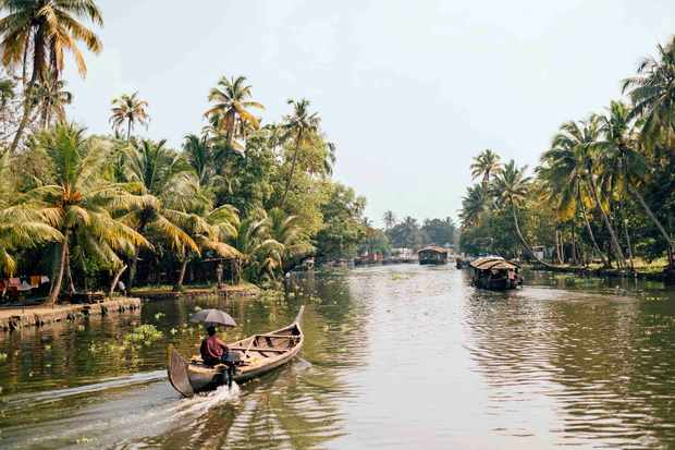 People travelling in traditional boats on river, Kumarakom, Kerala, India
