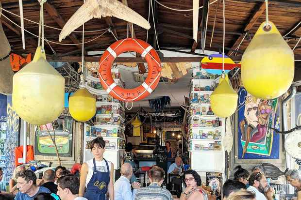 A busy restaurant with buoys hanging from ceiling