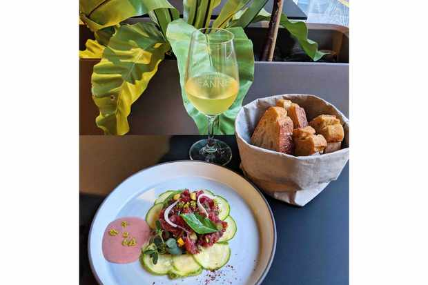 A glass of wine, basket of bread and plate of tartare at Madame Jeanne Marseille