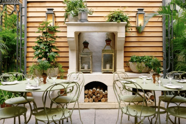 Green garden furniture in a plant-filled courtyard at The Whitby hotel New York