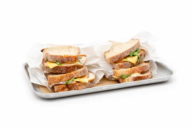 A silver tray topped with sourdough sandwiches with cheese and turkey in the middle