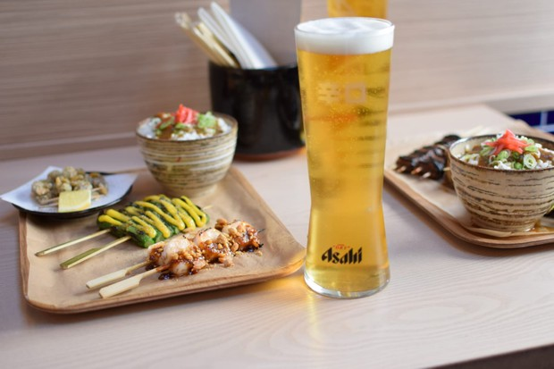 A wooden board has meat skewers on it, with a bowl of rice topped with brown curry sauce. There is a large pint glass filled with orange beer