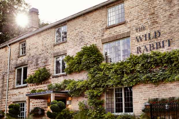The Wild Rabbit exterior – a Cotswold stone building with greenery spread across it