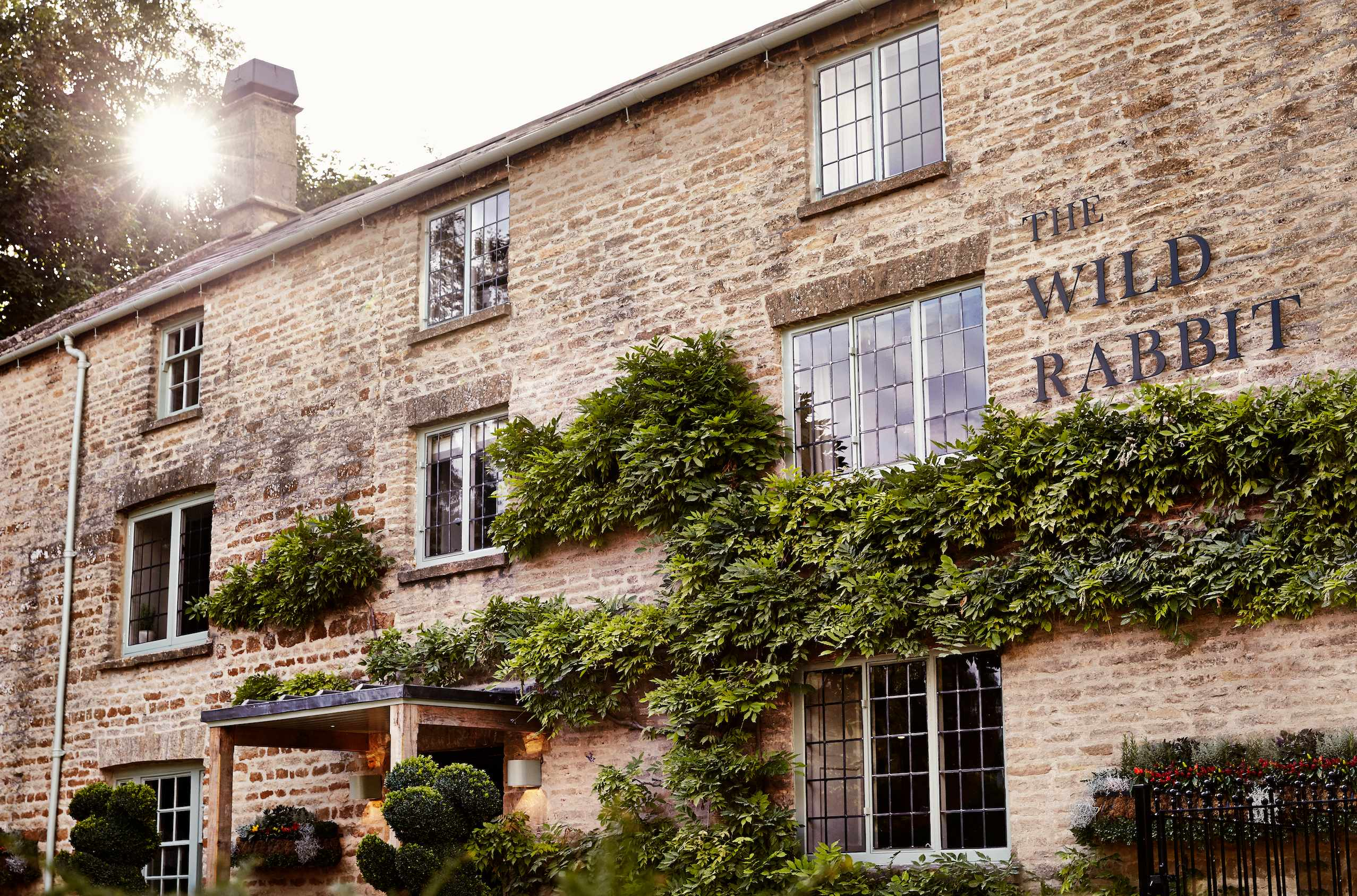 The Wild Rabbit exterior –a Cotswold stone building with greenery spread across it