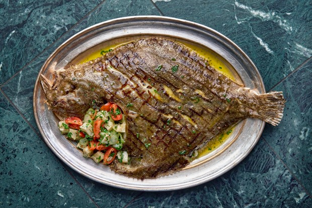 A blue marble background has a silver tray on top. On top is a whole turbot fish with a bearnaise sauce