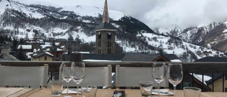 A table with a view of a church and snowy mountains