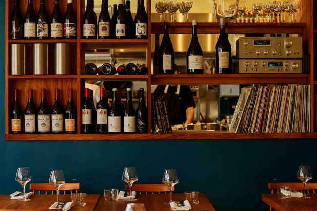 Shelves of wine and vinyl and tables set for dinner at Levan Peckham