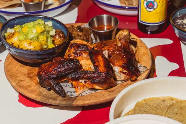 A wooden board with roast chicken