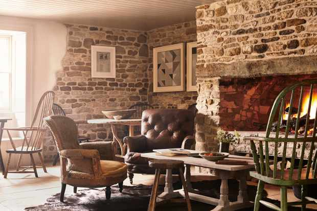 A roaring fire and squidgy leather chairs in the pub area of the Wild Rabbit, Kingham