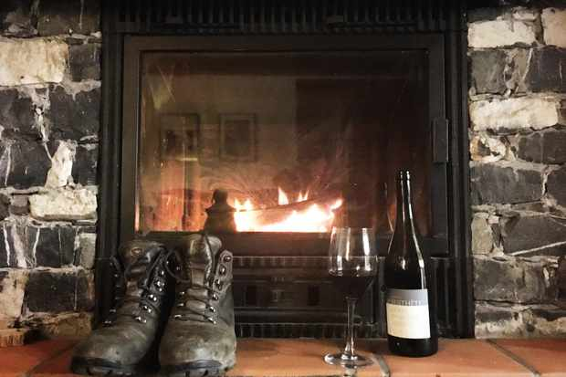 Boots and a bottle of wine in front of a fireplace