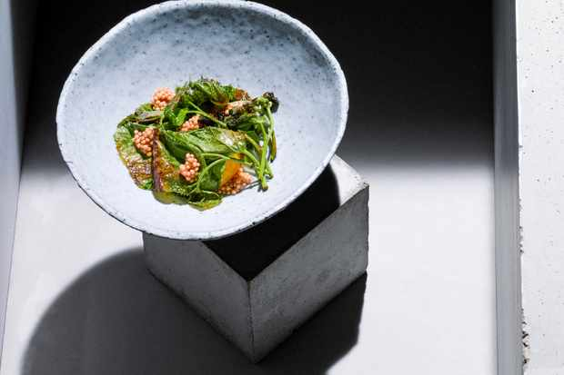 A dish of greens in a pale blue bowl