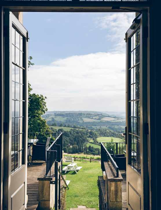 Double doors look out over the Bath countryside. To the side is a terrace with tables and chairs