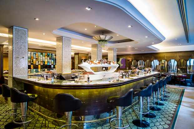 A large central bar area has high stools. There is a green carpet and a tiled wall in the background