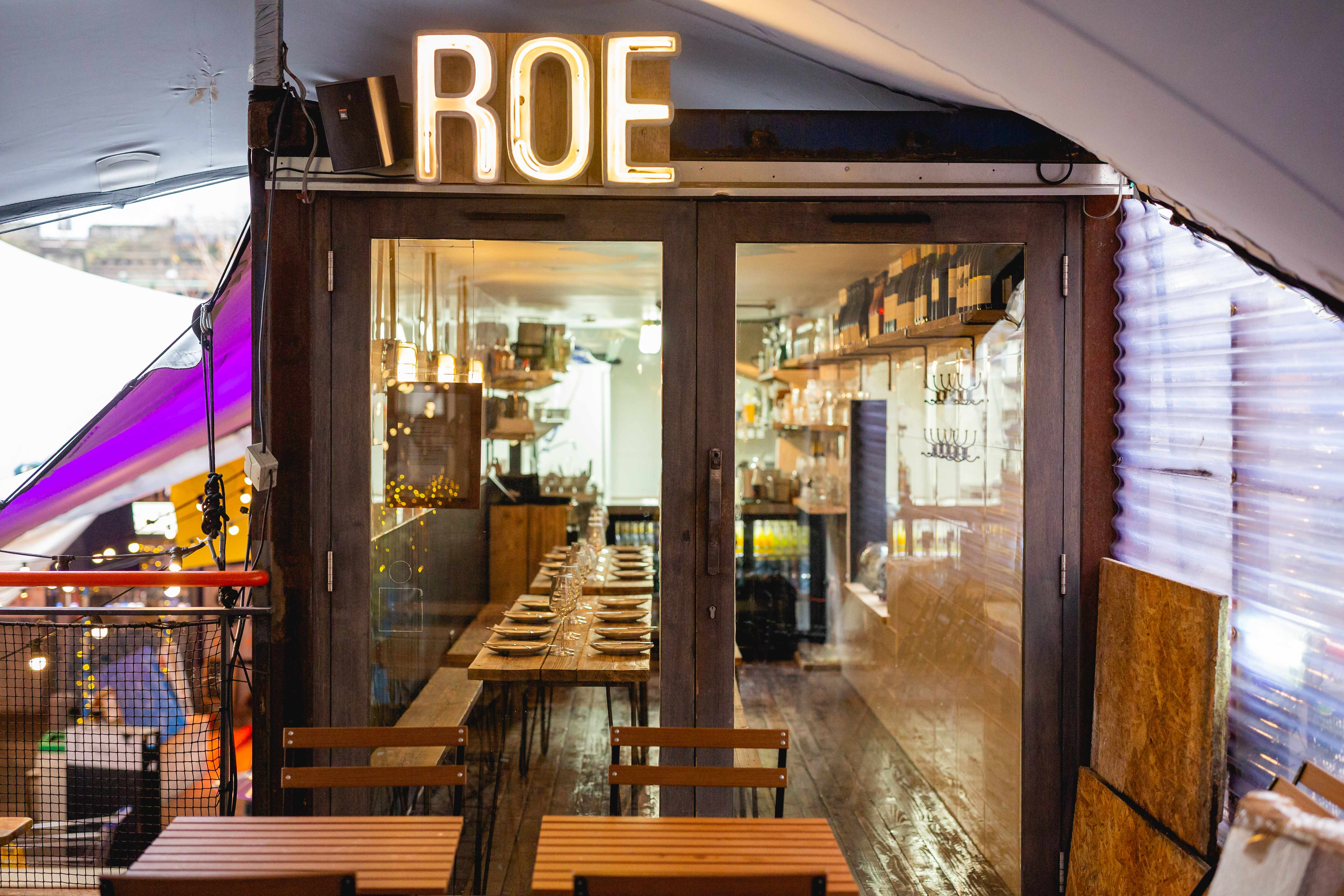 Doorway of Roe Pop Brixton with view of long wooden tables inside