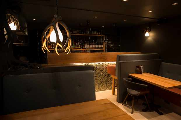 A dark room with a bar, tables and chairs