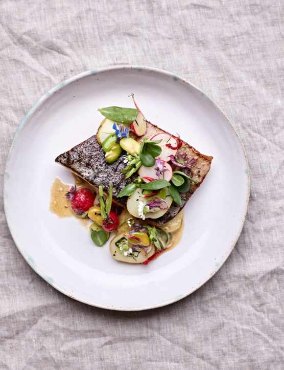 A grey linen napkin is topped with a white plate. On top of the plate is a fillet of crispy fish topped with slices of potatoes, radish and grennery