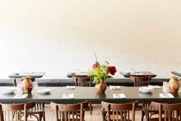 White washed walls with long sharing tables. Vases of flowers are sat on the tables