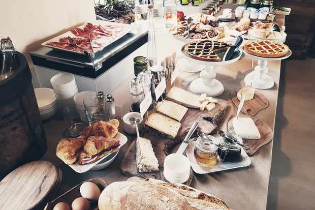 A lavish breakfast spread of croissants, bread, cheese, jams, waffles, charcuterie and eggs at Langhe Country House, Italy