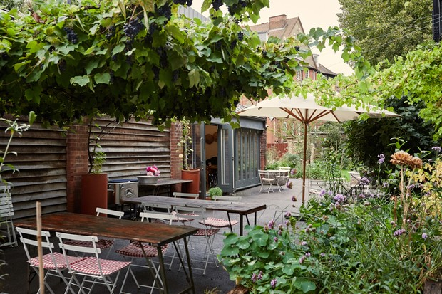 A courtyard garden has picnic style tables and chairs