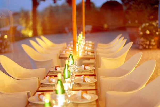 A long wooden table with white linen chairs. There are flickering candles on the table and plates with napkins on