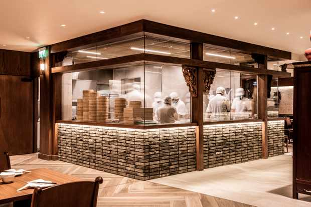 Inside Din Tai Fung is a glass room where cooks in masks prepare dumplings