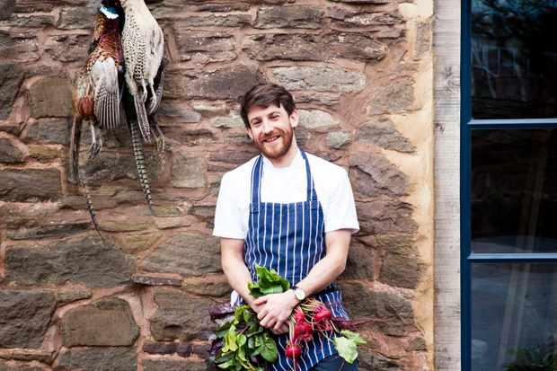 A dark haired man in a blue and white striped apron stands against a stone brick wall. He is holding a bunch of radishes and there a pheasants hanging behind him