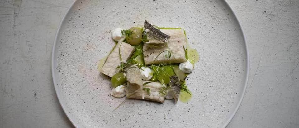 A grey circular plate is topped with fish, dots of green apple sauce and crispy fish skin
