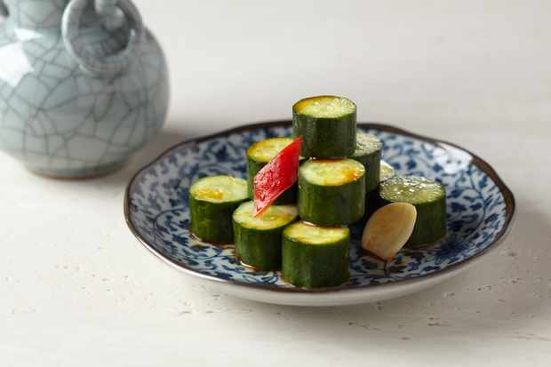 A decorative blue plate is topped with chunks of pickled cucumber. There is a teapot in the background