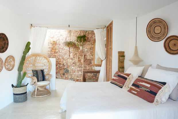 A white washed stone bedroom with a double bed, hanging hanging and aztec print cushions