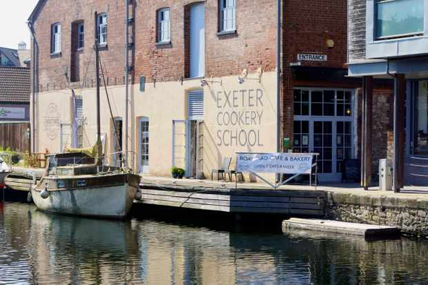 There is a river with a boat on it. Sat on the river is an old building with the words Exeter Cookery School written on it