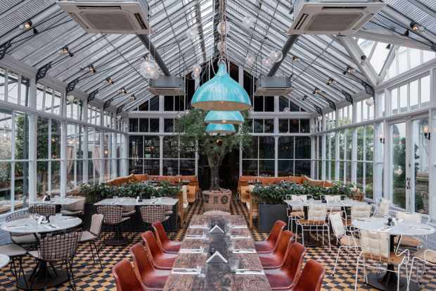 A greenhouse room with a tiled floor. There is a long table down the centre and smaller tables for four in the rest of the room