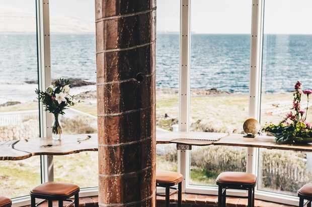 Floor to ceiling glass windows look out over the seat from Hotel Havgrim. There are brown bar stools facing outwards looking towards the sea