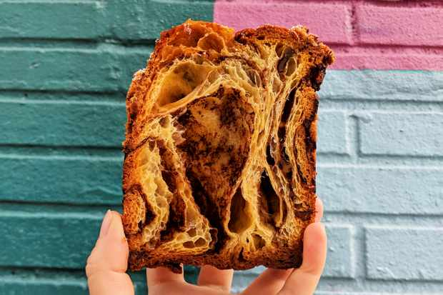 Babka in front of a colourful brick wall at Zak the Baker Miami