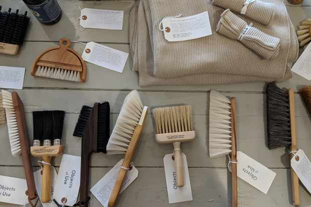 A wooden table is topped with various sized brushed, all with luggage labels on explaining what each brush is for