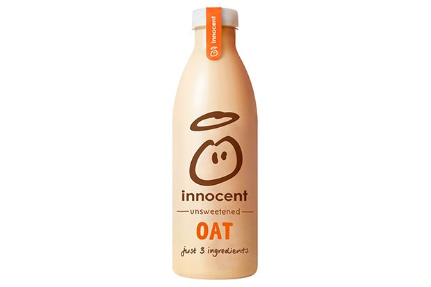 A clear bottle filled with beige oat milk with the Innocent angel logo on the front