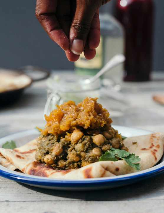 A white plate with a blue rim is topped with a folded roti. On top of the roti is a thick chickpea curry and there are a pair of hands sprinkling seasoning on top
