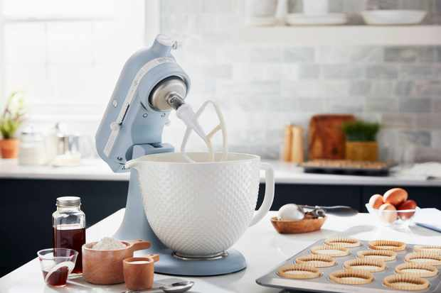 A misty blue kitchenaid mixer with a glass bowl is stood on a work surface. On the work surface is a tray of muffins