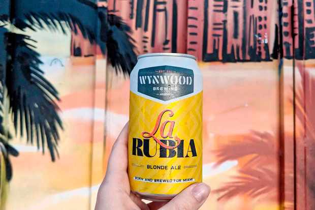 A can of beer held up against a mural at Kush Wynwood