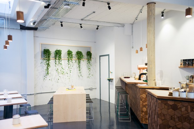 A minimal space with grey white washed walls has hanging plants on. There are sturdy wooden tables with stool seats