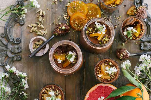 Five pots of chocolate, orange and cardamom mousse are topped with orange slices and edible flowers. There are slices of orange and grapefruit in the images and two spoons for scoops of mousse on