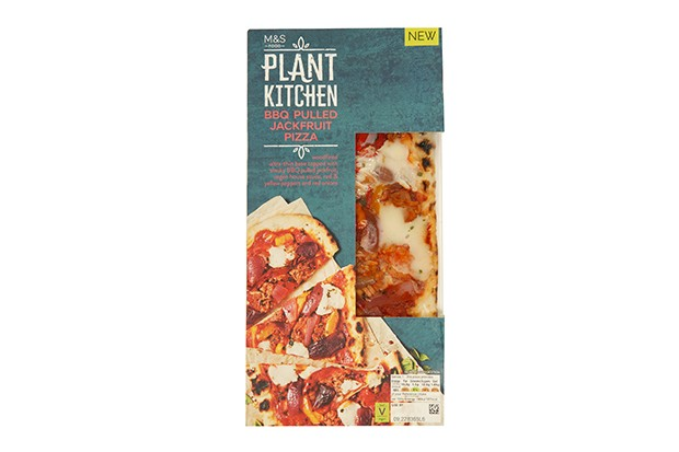 A long blue cardboard packet is filled with an uncooked vegan BBQ pulled jackfruit vegan pizza