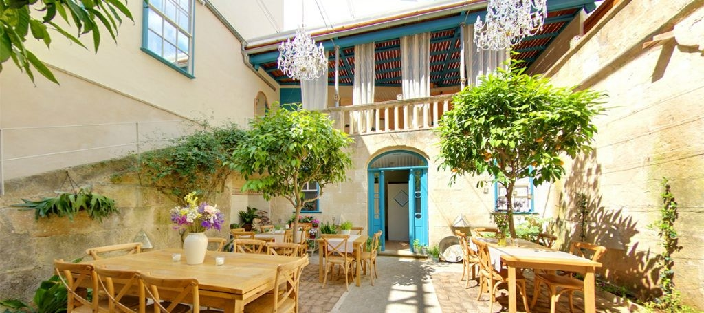 A sun-dappled courtyard in Menroca with wooden tables and chairs dotted around the courtyard. In the background is a stone building with blue doors, a veranda and two trees